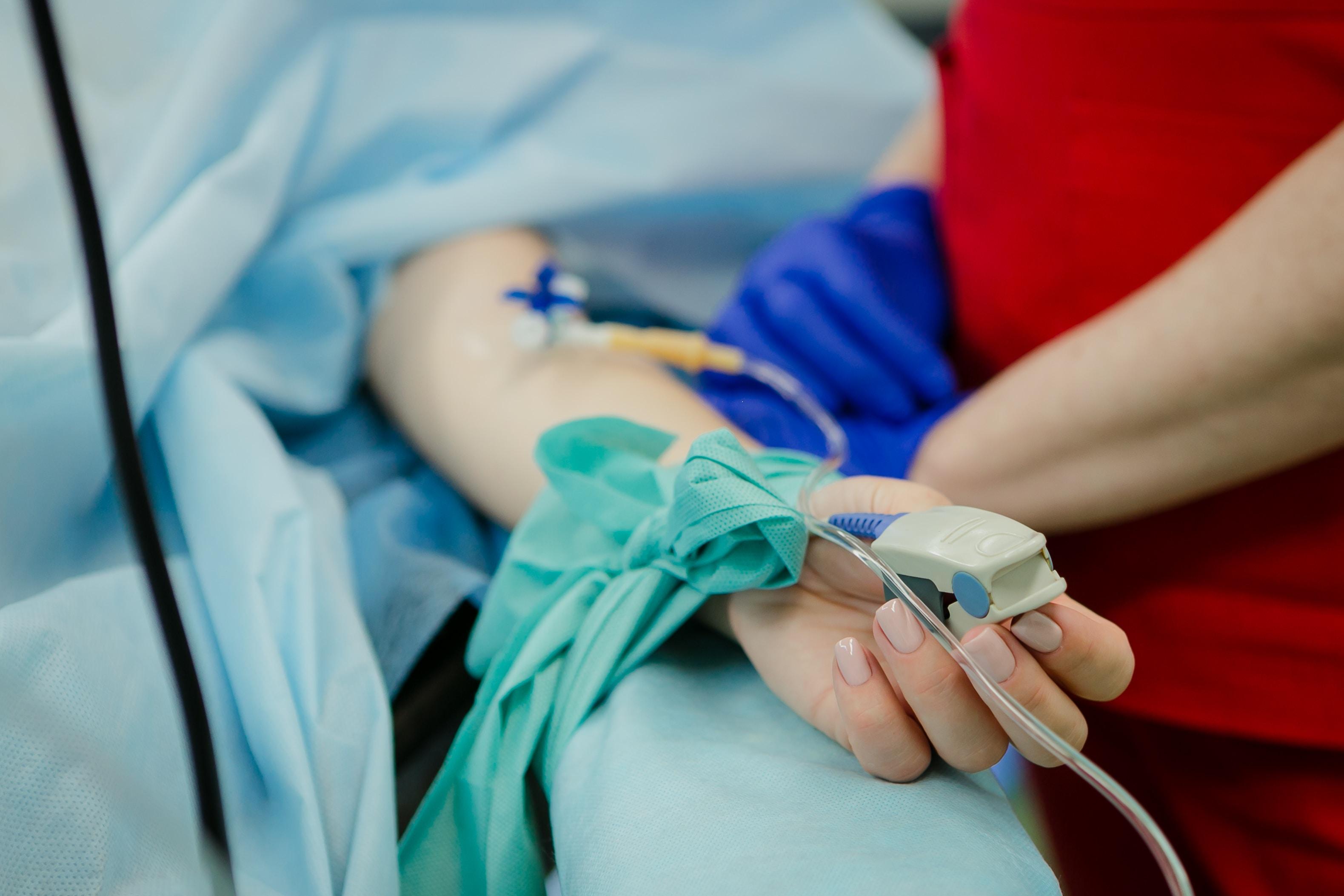 Woman's hand on hospital bed, Photo Credit: Unsplash / Olga Kononenko