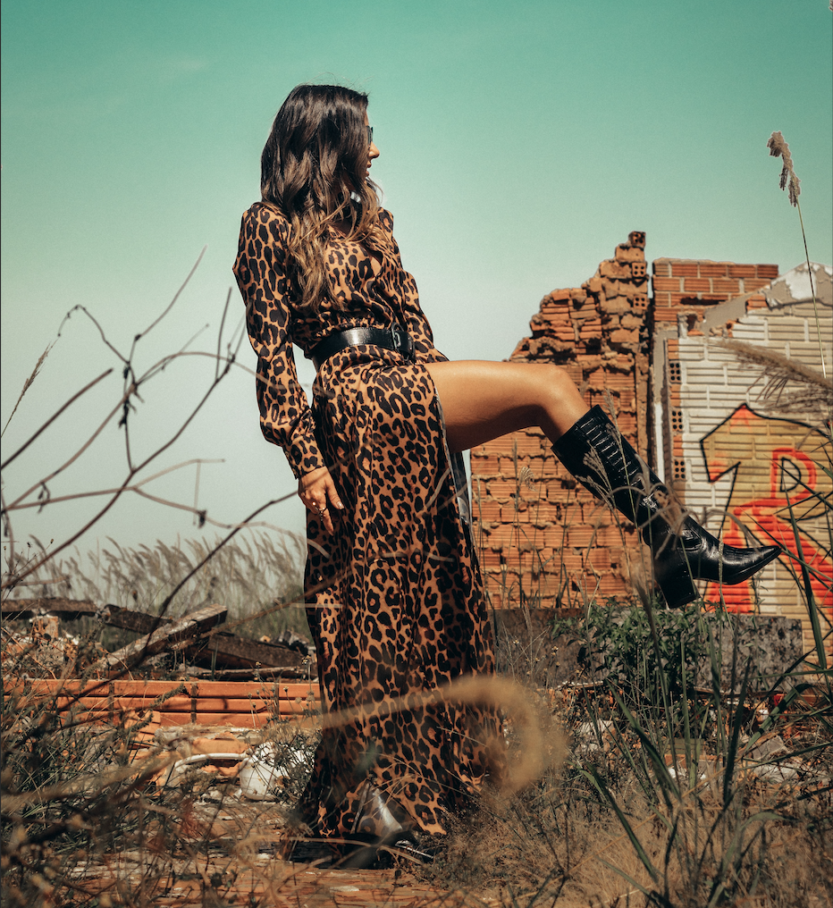 A woman wearing a leopard print dress and boots