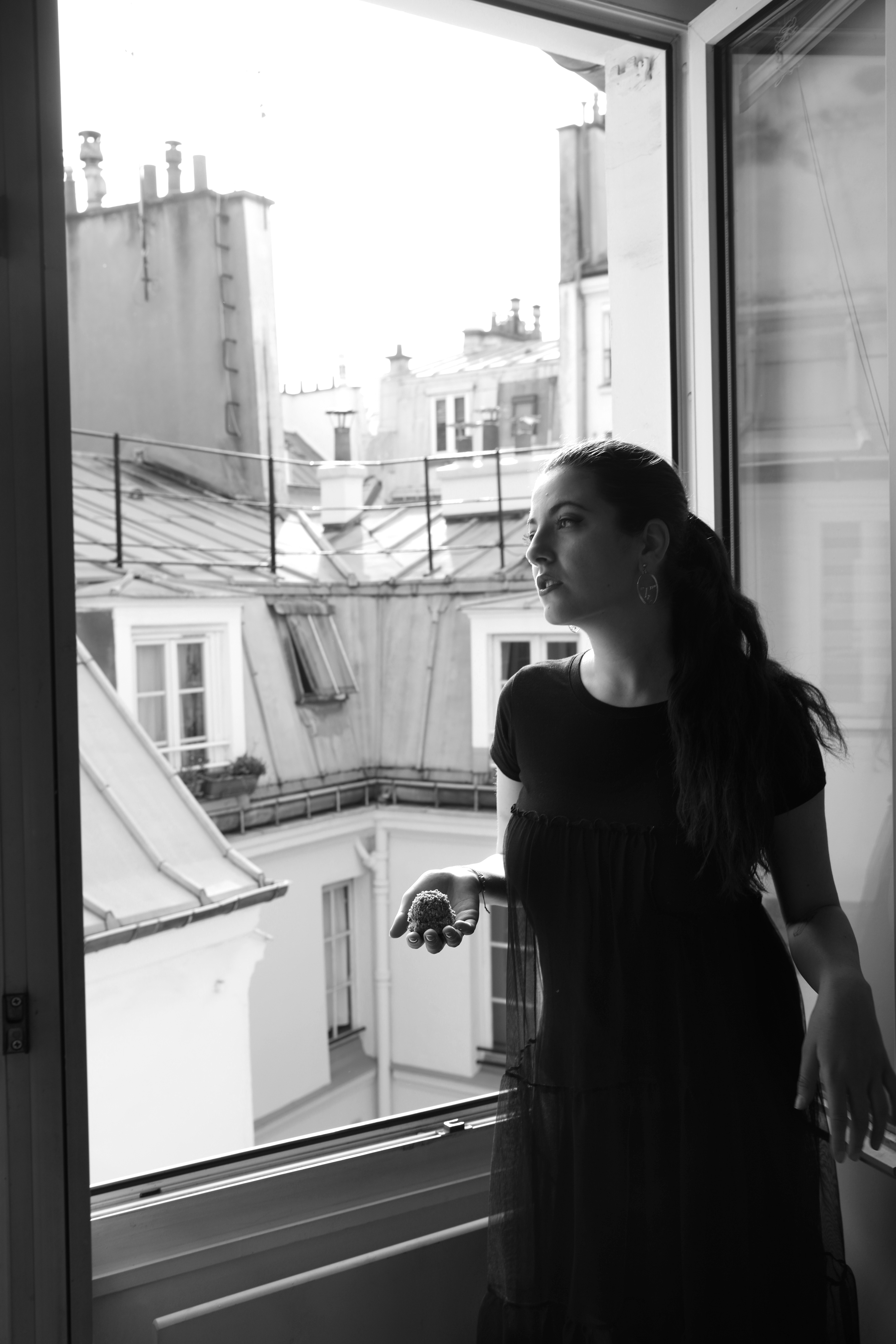 A brunette model standing by a window