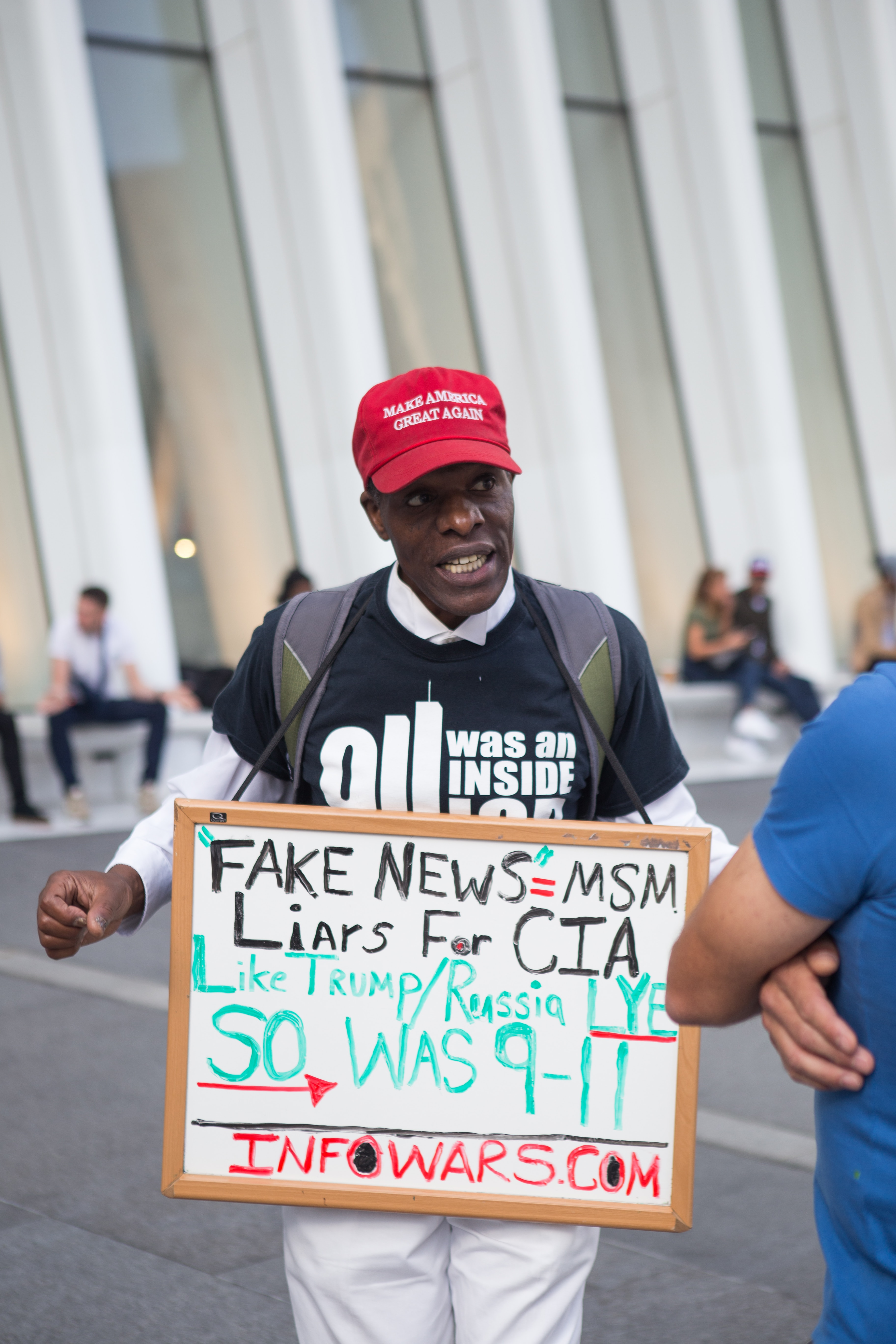 Man holding a sign with conspiracy theories wearing a Make America Great Again hat / Photo credit: Capturing the human heart on Unsplash