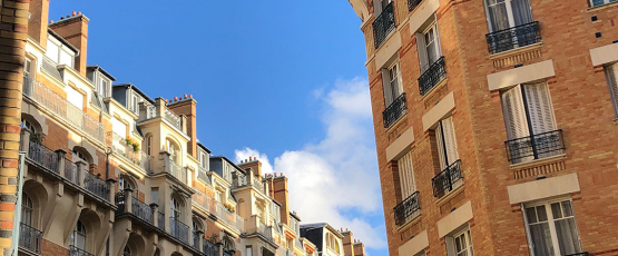 Looking up at red brick buildings which line a Paris street