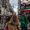 Woman Wearing Green Jacket in Pedestrian Lane During Daytime