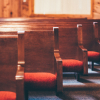 Red upholstered pews are seen from the front of a church.