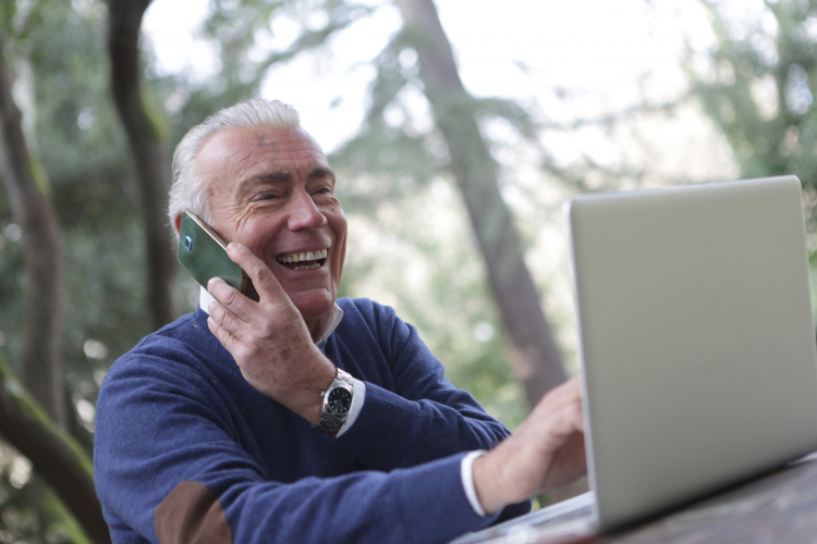 An older man uses a laptop with one hand, while his other holds a smartphone to his ear