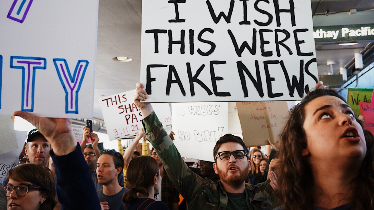 """""""I wish this was Fake News"""" sign at the LAX protest against Trump's muslim ban. / Photo credit: Kayla Velasquez on Unsplash"""
